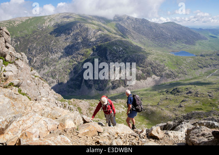 Hikers scrambling up Crib Goch above Llanberis Pass at start of Snowdon Horseshoe in Snowdonia North Wales UK Britain - Stock Photo
