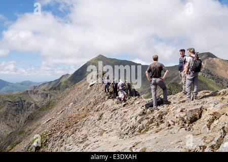 Hikers on Crib Goch knife edge ridge top scramble at start of Mount Snowdon Horseshoe in mountains of Snowdonia - Stock Photo