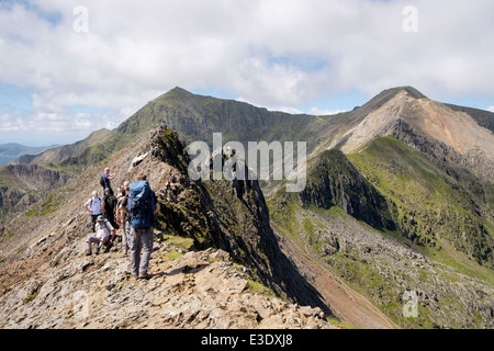 Walkers on Crib Goch ridge top scramble on the Snowdon Horseshoe with Crib y Ddysgl and Mt Snowdon peak in Snowdonia - Stock Photo