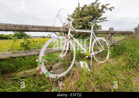 'Ghost Bike' on a rural road in tribute to a cyclist killed in a road traffic accident. - Stock Photo
