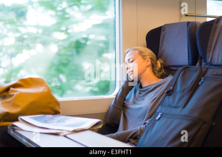 Lady traveling napping on a train. - Stock Photo