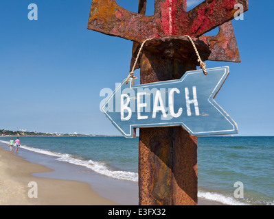 Wooden beach sign hanging on rustic metal post with couple in background strolling at waters edge Sandbanks Dorset - Stock Photo
