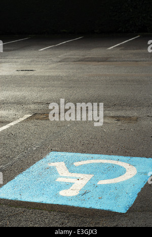 Space reserved for handicapped drivers in an empty car parking - Stock Photo