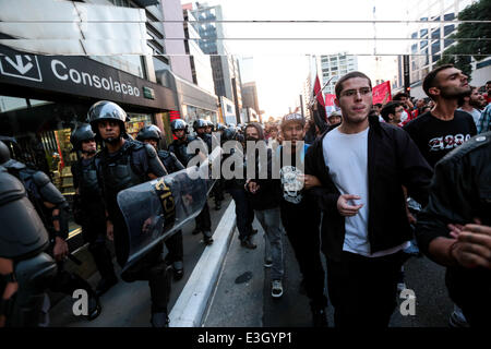 Sao Paulo, Brazil. 23rd June, 2014. Protesters against the 2014 FIFA World Cup march side by side with riot policemans - Stock Photo