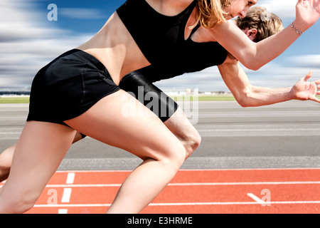 Race of male and female track and field athletes on airport runway - Stock Photo