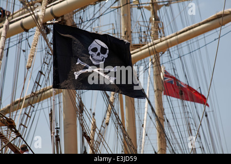 Jolly Roger pirate flag flying on tall ship at Harry Paye Day, Poole's annual celebration of its favourite pirate - Stock Photo