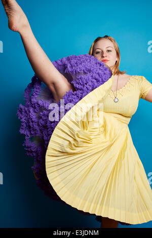 Young Woman Wearing Yellow Dress Lifting One Leg - Stock Photo