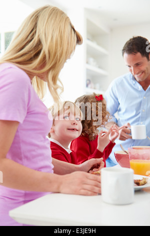 Family Having Breakfast In Kitchen Before School - Stock Photo
