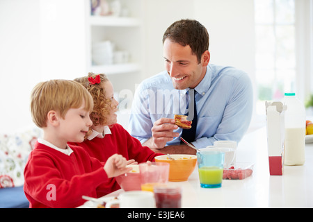 Father And Children Having Breakfast In Kitchen Together - Stock Photo