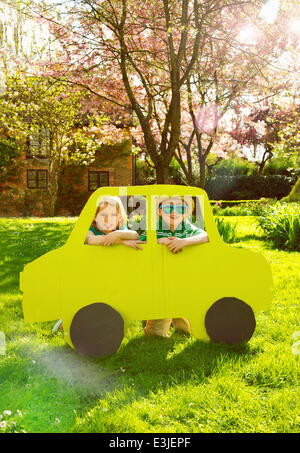 Boy and Girl Looking out of Cardboard Car Window - Stock Photo