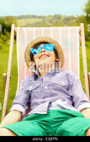 Smiling Boy Wearing Straw Hat and Sunglasses Sitting on Deck Chair - Stock Photo
