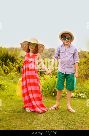 Boy and Girl Wearing Straw Hat and Sunglasses Smiling - Stock Photo