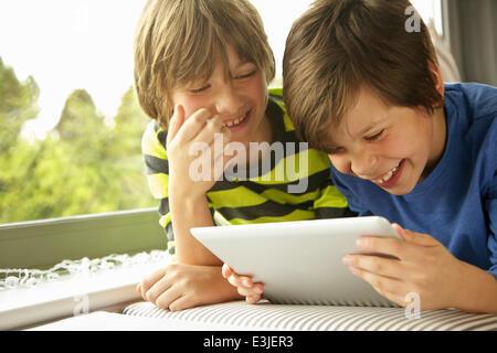 Boys Using Digital Tablet Smiling - Stock Photo