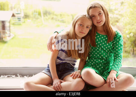 Two Young Girls Sitting on Window Sill - Stock Photo