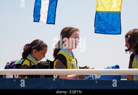 Brownies boarding ferry to go across to Brownsea Island in Poole Harbour, Dorset in June - Stock Photo