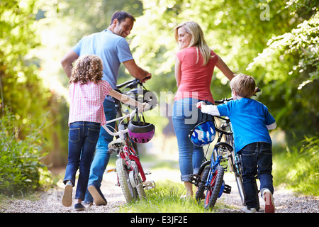 Family Pushing Bikes Along Country Track - Stock Photo