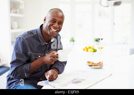 African American Man Eating Breakfast And Reading Newspaper - Stock Photo