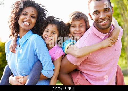 African American Parents Giving Children Piggyback Rides - Stock Photo
