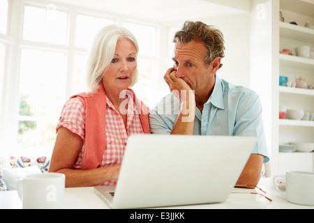 Worried Middle Aged Couple Looking At Laptop - Stock Photo