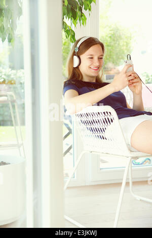 Teenage Girl Wearing Headphones Using Smartphone - Stock Photo