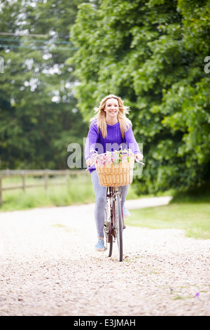 Teenage Girl Riding Bike Along Country Lane - Stock Photo