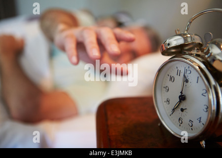 Couple In Bed With Man Reaching To Switch Off Alarm Clock - Stock Photo