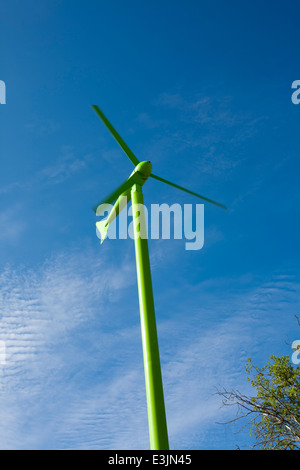 Green wind turbine against blue sky - Stock Photo