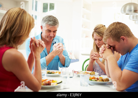 Family Saying Prayer Before Eating Meal At Home Together - Stock Photo