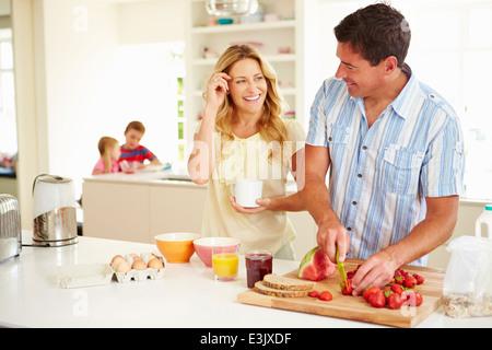 Parents Preparing Family Breakfast In Kitchen - Stock Photo