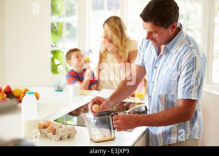Father Preparing Family Breakfast In Kitchen - Stock Photo