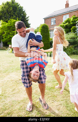 Family Having Fun Playing In Garden - Stock Photo