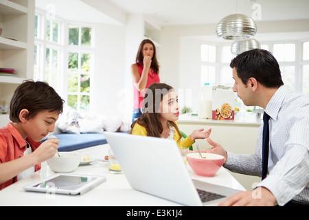 Family Using Digital Devices Having Argument Over Breakfast - Stock Photo