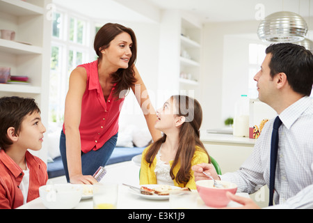 Family Having Breakfast Before Husband Goes To Work - Stock Photo