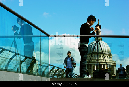 Photographer on Millennium Bridge photographing St Paul's Cathedral seen through engraved glass with reflection - Stock Photo