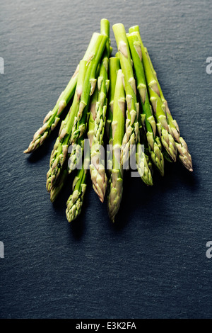 Bunch of fresh asparagus on slate background - Stock Photo