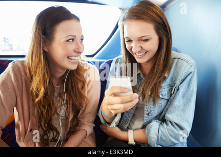 Two Young Women Reading Text Message On Bus - Stock Photo
