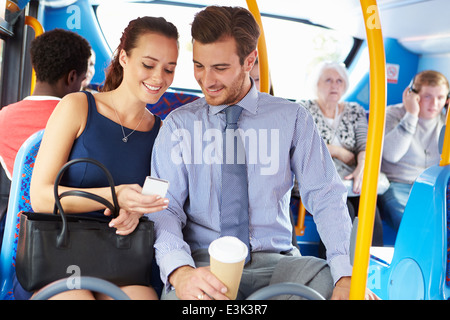 Businessman And Woman Looking At Mobile Phone On Bus - Stock Photo