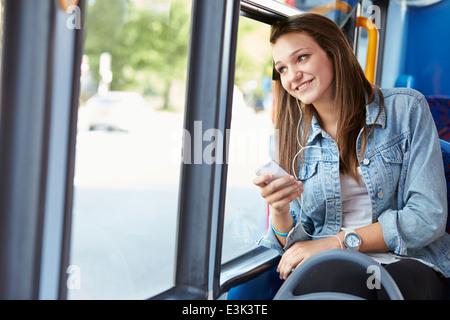 Teenage Girl Wearing Earphones Listening To Music On Bus - Stock Photo