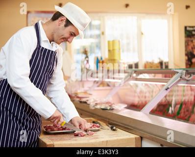 Butcher Preparing Meat In Shop - Stock Photo