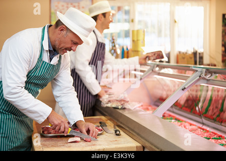 Two Butchers Preparing Meat In Shop - Stock Photo