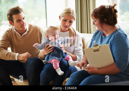 Social Worker Visiting Family With Young Baby - Stock Photo