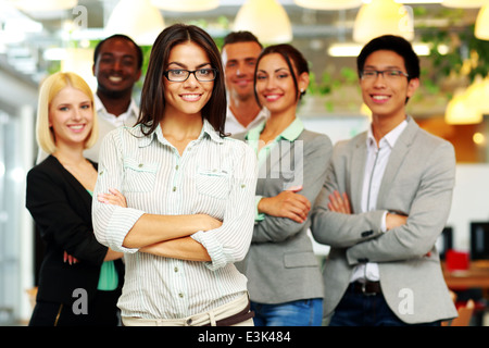 Smiling group of co-workers standing in office - Stock Photo