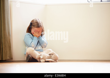 Unhappy Child Sitting On Floor In Corner At Home - Stock Photo