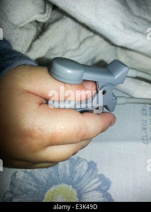 baby connected to a pulse oximeter on his finger. Pulse oximeters measure a patient's pulse rate and blood oxygen - Stock Photo