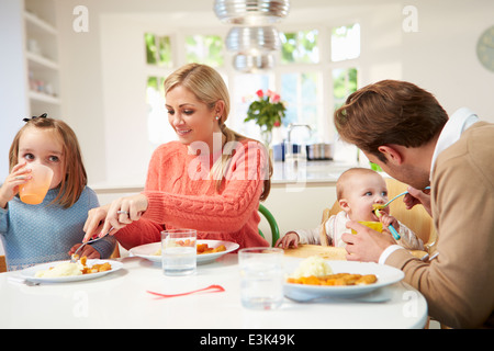 Family With Young Baby Eating Meal At Home - Stock Photo