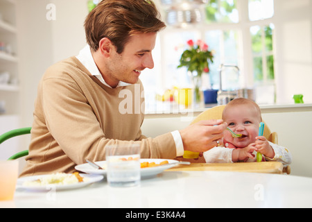 Father Feeding Baby Sitting In High Chair At Mealtime - Stock Photo