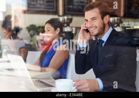 Businessman Using Mobile Phone And Laptop In Coffee Shop - Stock Photo