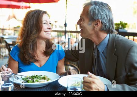 Mature Couple Enjoying Meal At Outdoor Restaurant - Stock Photo