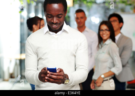 Happy businessman using smartphone in front of colleagues - Stock Photo