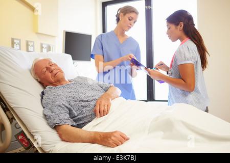 Medical Team Meeting As Senior Man Sleeps In Hospital Room - Stock Photo